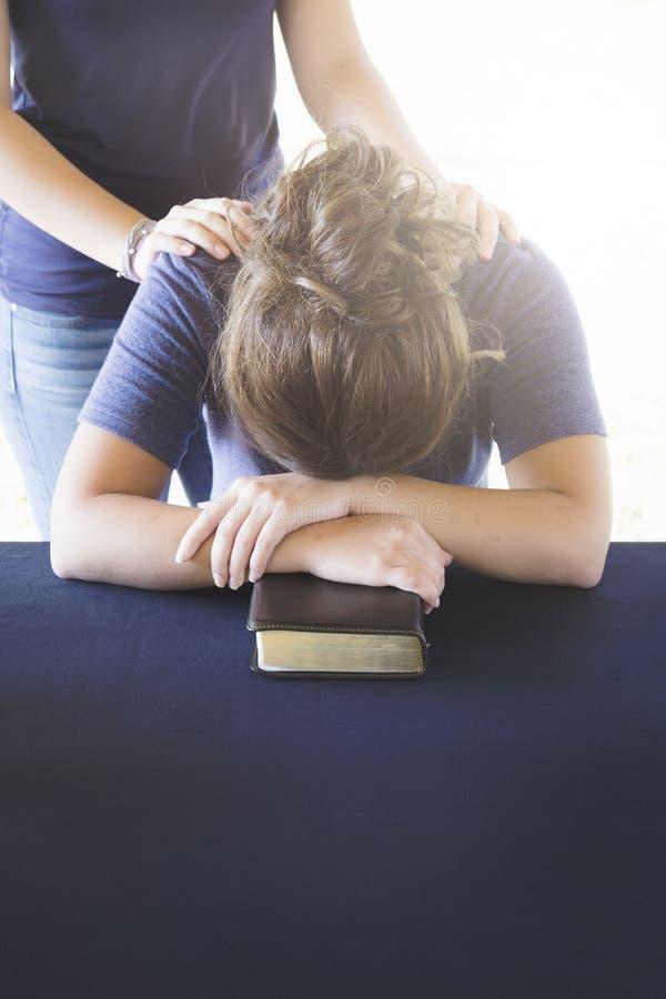 Conforto della donna afflitta durante lo studio della bibbia fotografie stock libere da diritti