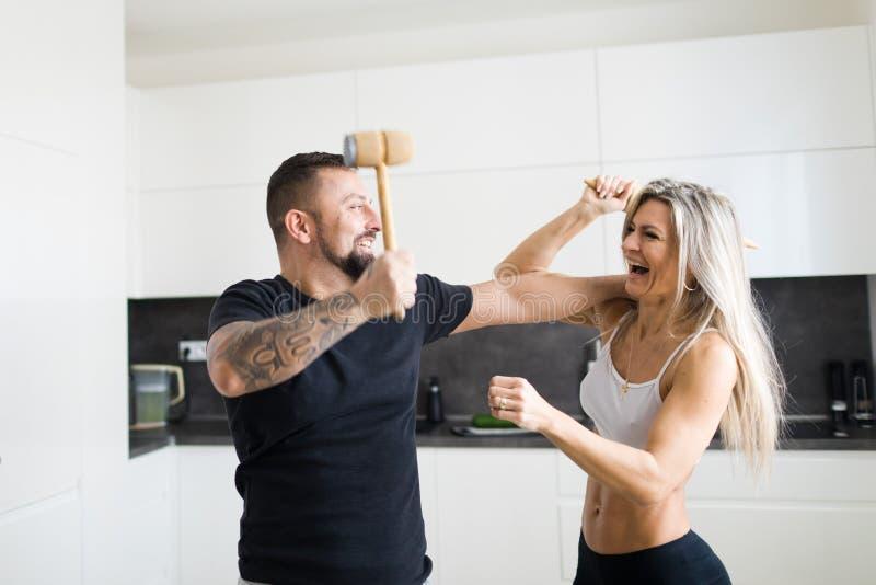 Confrontação do marido e da esposa na cozinha - tendo um divertimento junto fotografia de stock