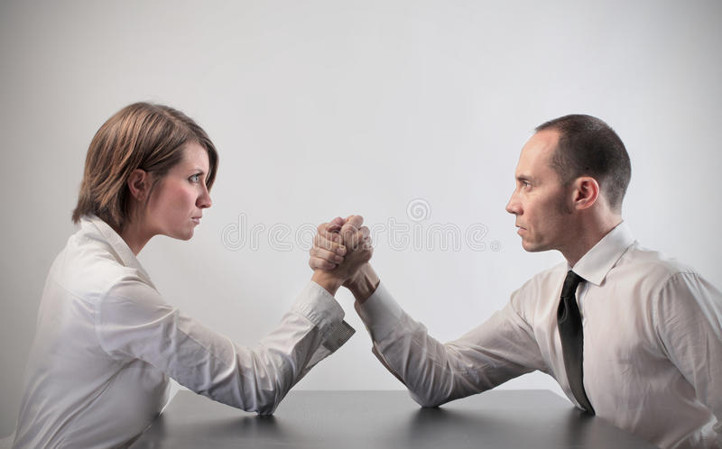 Confrontation. Couple of business people doing arm wrestling royalty free stock photography