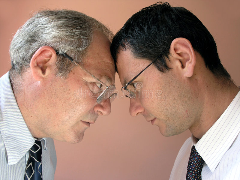 Confrontation. Two businessman from different generations. Conflict of powers stock photo