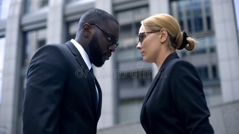Confrontation of business rivals, partners leaning foreheads, hate and envy. Stock photo royalty free stock photos
