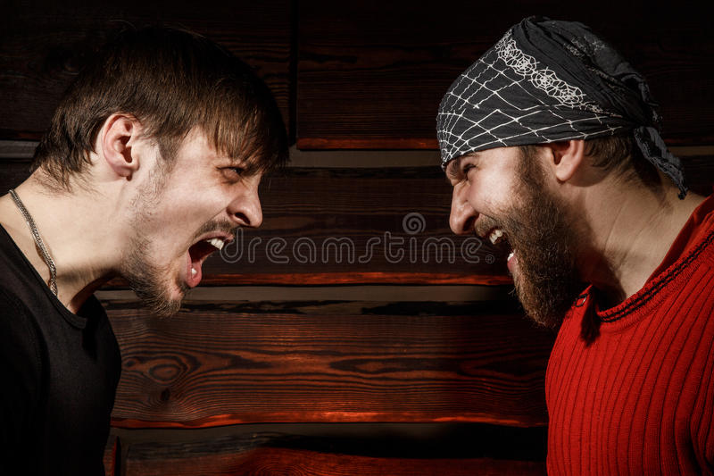 Confrontation. Conceptual photo. Two brutal men looking into each other's eyes royalty free stock image