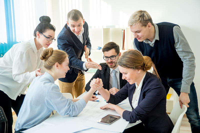 Confrontation in office. Two workers confront each other and arm wrestle stock photography