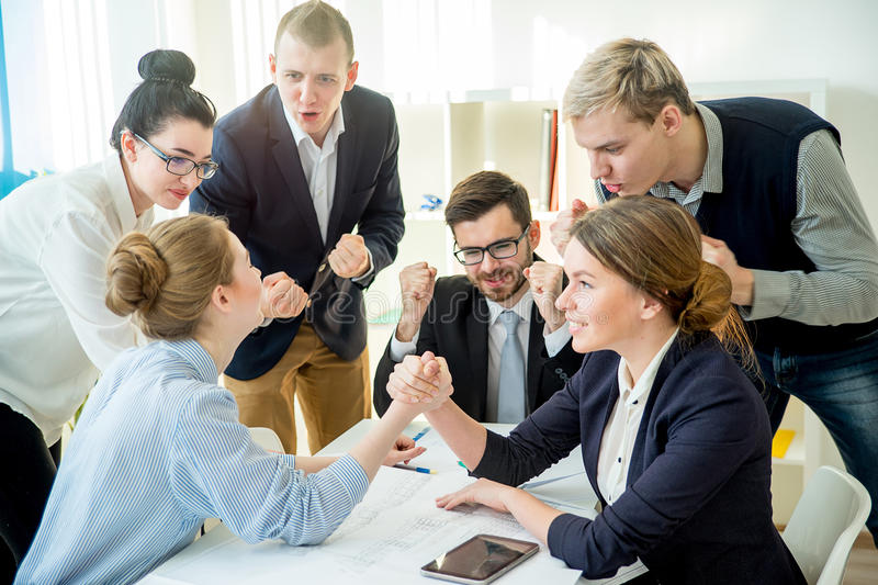 Confrontation in office. Two workers confront each other and arm wrestle royalty free stock image