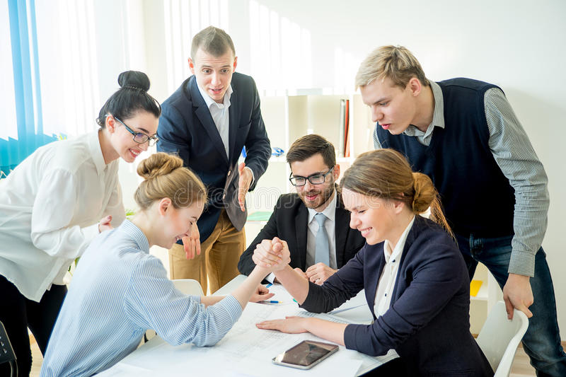 Confrontation in office. Two workers confront each other and arm wrestle stock photo