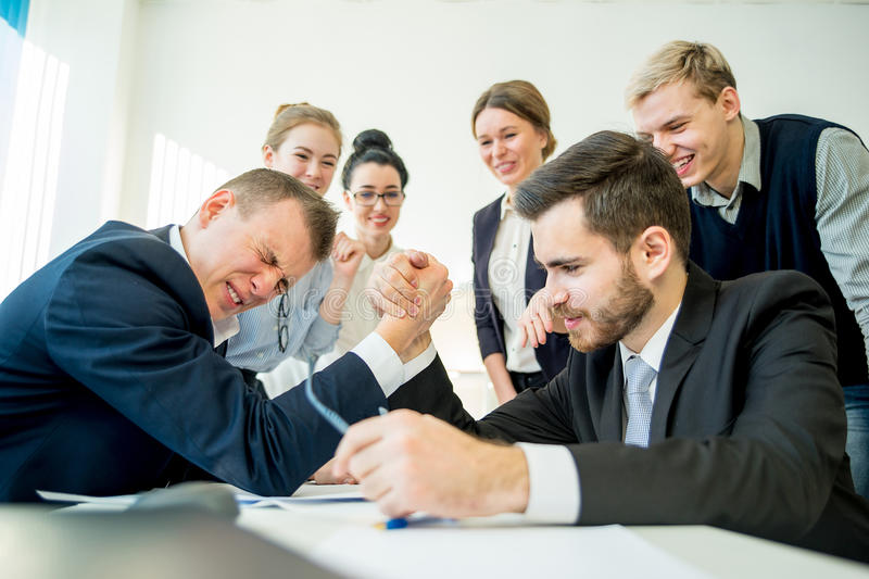 Confrontation in office. Two workers confront each other and arm wrestle stock photos