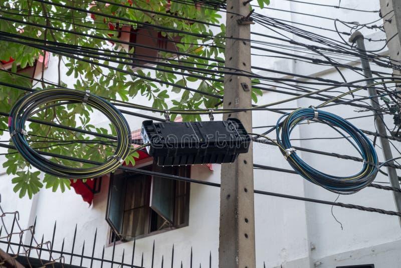 A confusão do cabo que é ficada situada ao longo da estrada para que o poder se use pela casa fotografia de stock