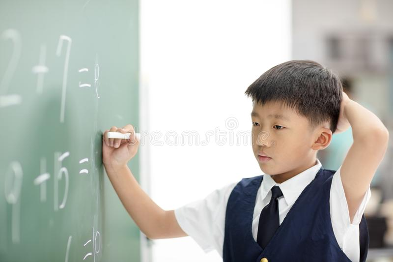 Confuse schoolboy try to answer question. Confuse asian schoolboy try to answer question on chalkboard stock photos