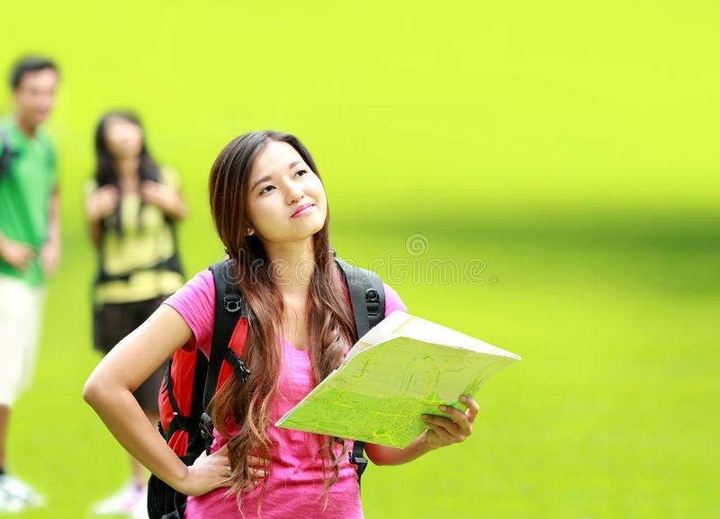 Confuse girl with map thinking something. Portrait of confuse asian girl camping in the park holding a map royalty free stock image