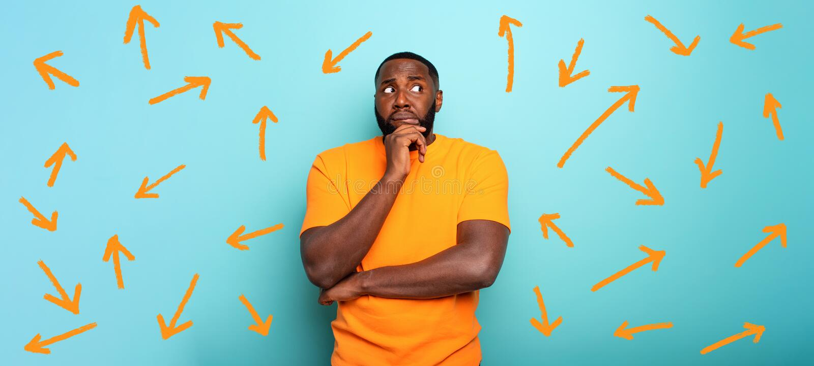 Confuse and pensive expression of a boy with many arrows to follow. cyan colored background stock photography
