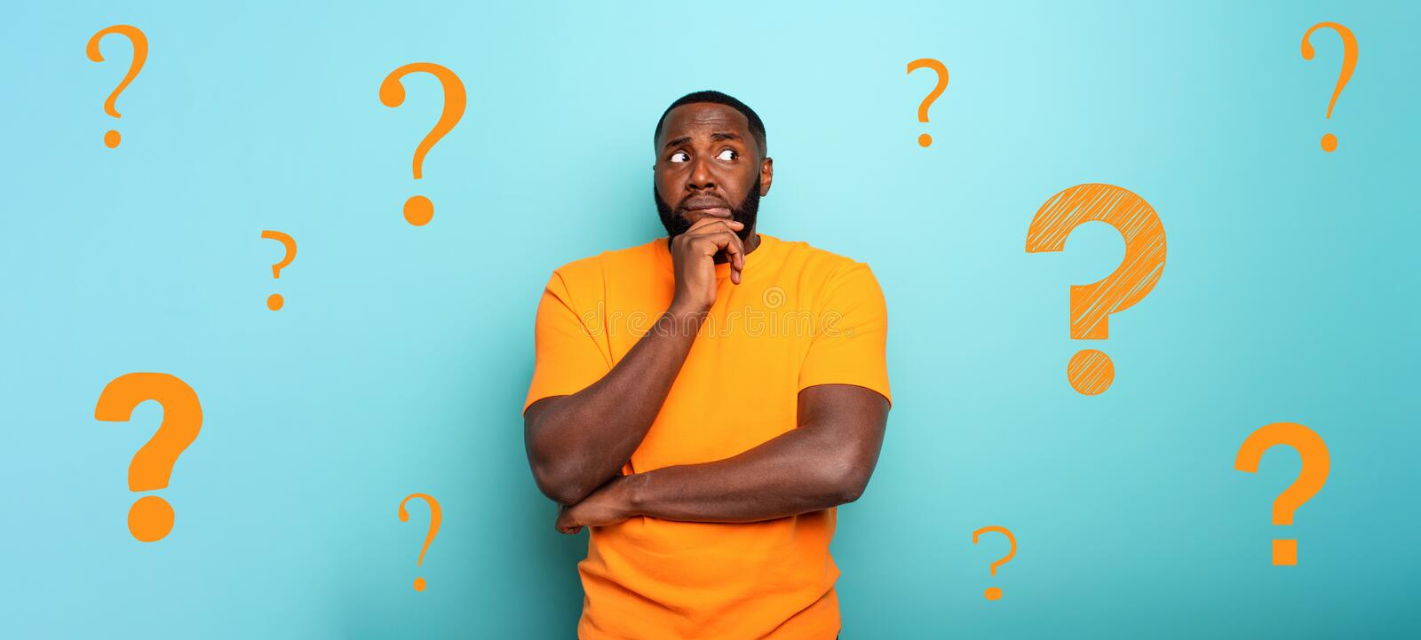 Confuse and pensive expression of a boy with many questions . cyan colored background stock image