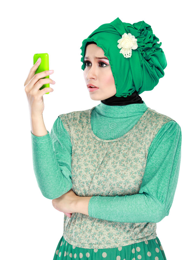 Confuse or shocked expression while looking to mobile phone. Portrait of asian woman with head scarf holding mobile phone. confuse or shocked expression stock photos