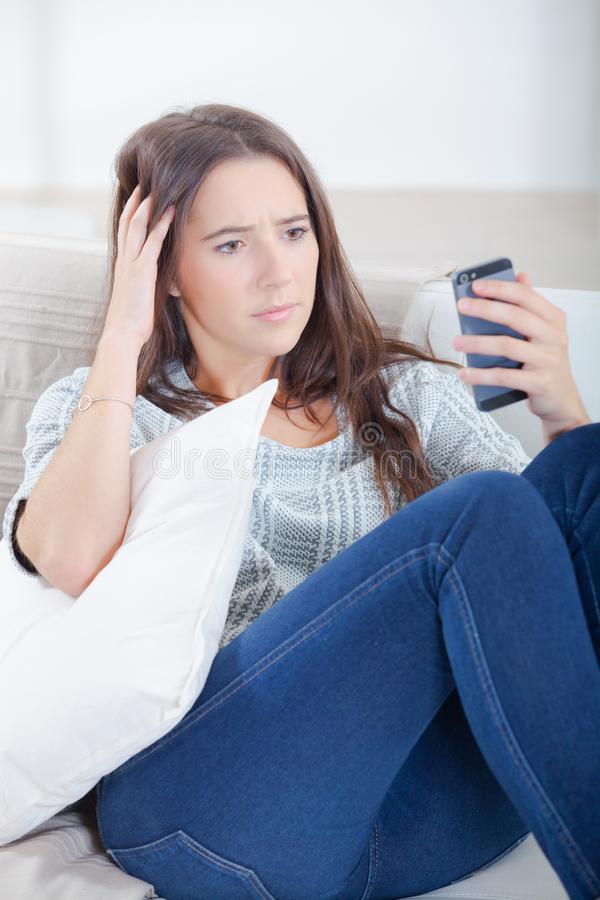 Confuse by the sms. Woman royalty free stock photos