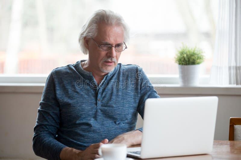 Confused åldrig man som svikas av negativ online-nyheterna arkivbilder