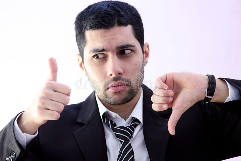 Confused арабский бизнесмен с thump поднимающим вверх и thump вниз стоковые фото