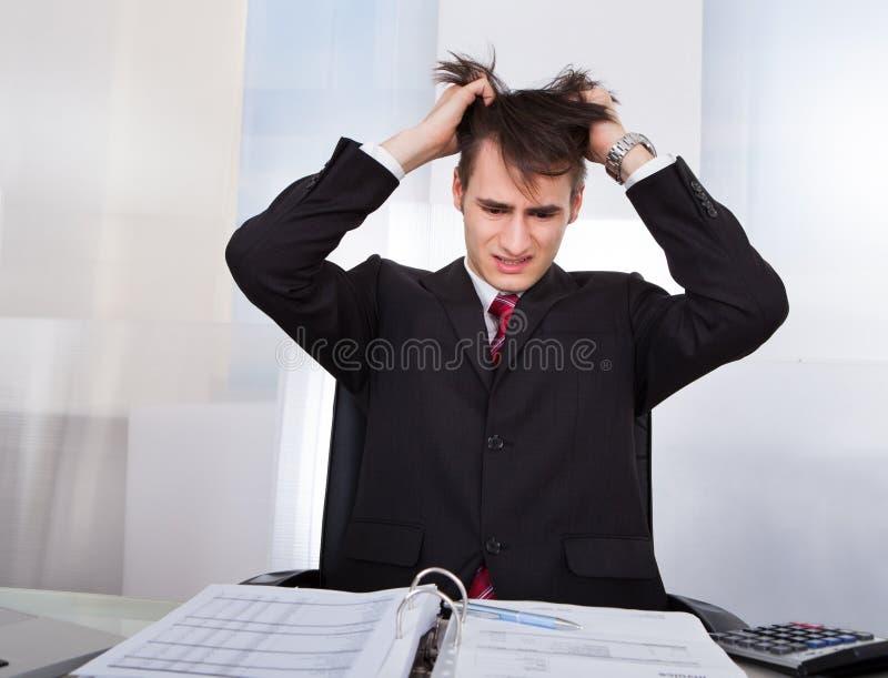 Confused бизнесмен вытягивая волосы пока высчитывающ финансы стоковая фотография