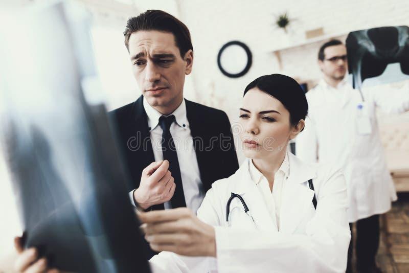 Confused бизнесмен смотрит рентгенографирование косточек Радиолог делает диагноз стоковое фото