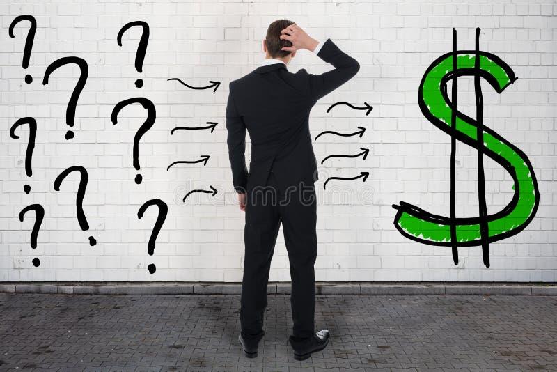 Confused бизнесмен смотря вопросительные знаки и знак доллара стоковые фото