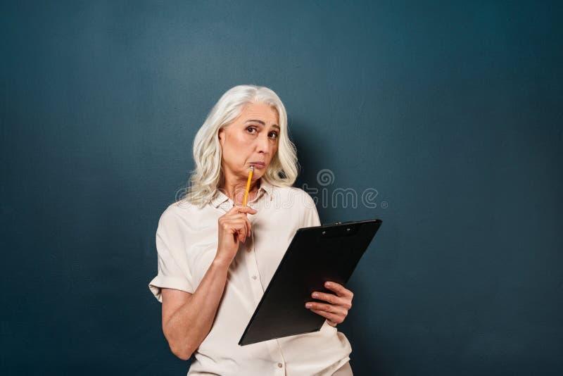 Confused зрелые примечания сочинительства старухи в доске сзажимом для бумаги стоковое фото rf
