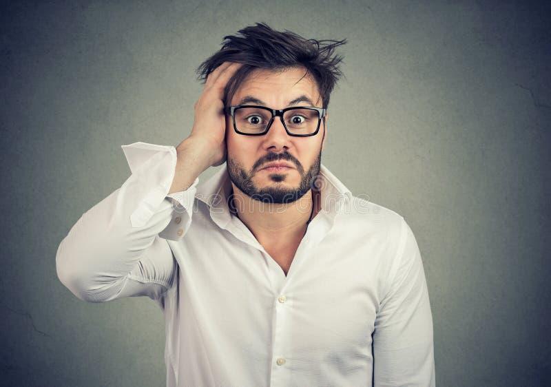 Confused молодой человек держа руку на голове стоковые фотографии rf