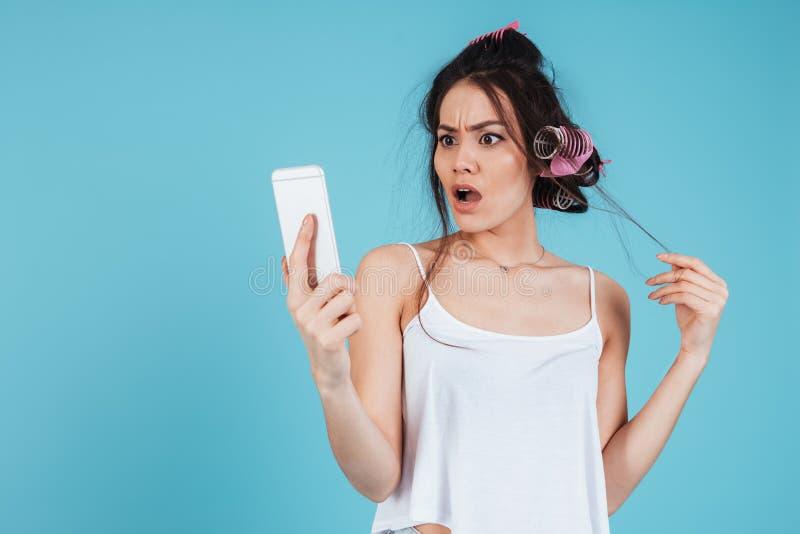 Confused молодая дама с curlers волос используя телефон стоковое изображение