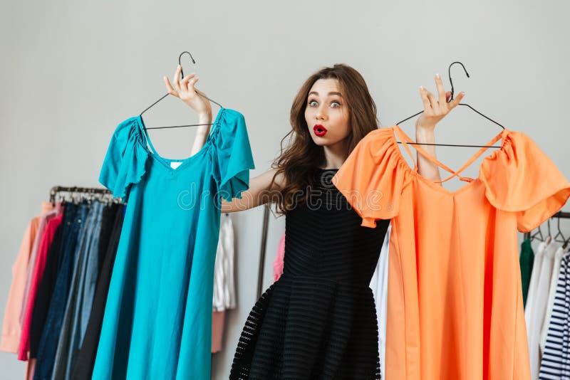 Confused молодая женщина выбирая между 2 платьями стоковое фото