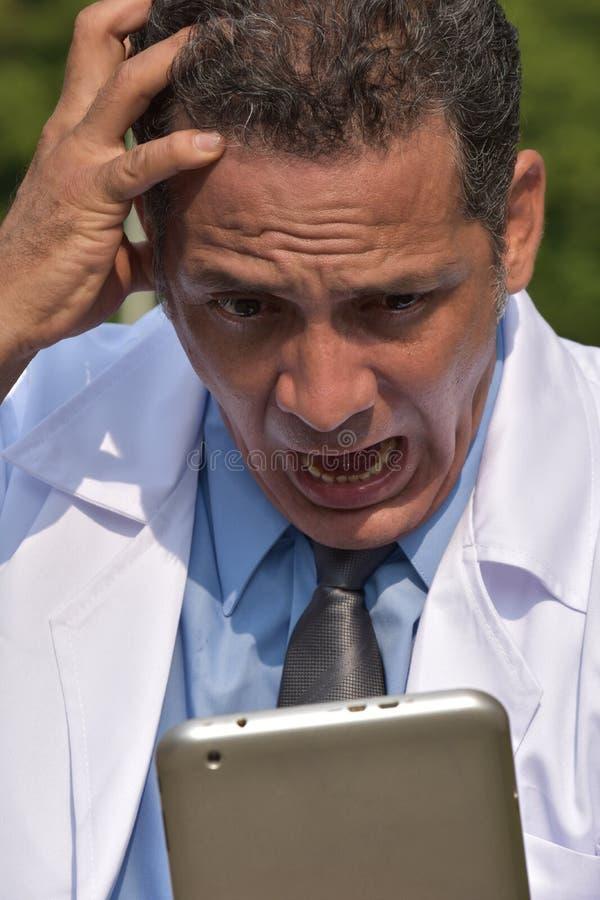 Confused мужской испанский доктор Используя Таблетка и стресс стоковое изображение rf