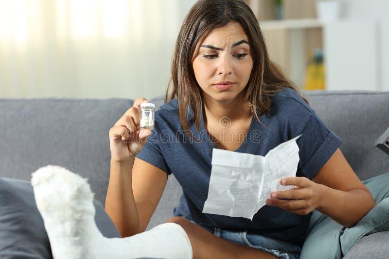 Confused неработающая девушка читая листовку пилюлек анальгетика стоковые изображения rf