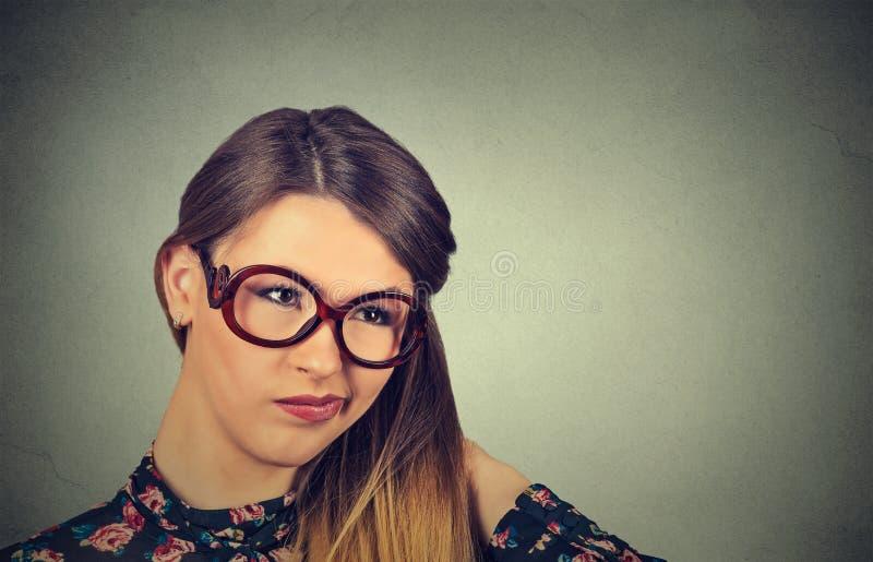 Confused скептичная женщина в стеклах думая смотреть озадачиванный стоковое фото rf
