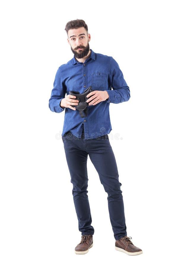 Confused скептичный равнодушный бизнесмен держа шлемофон виртуальной реальности смотря камеру стоковое фото rf