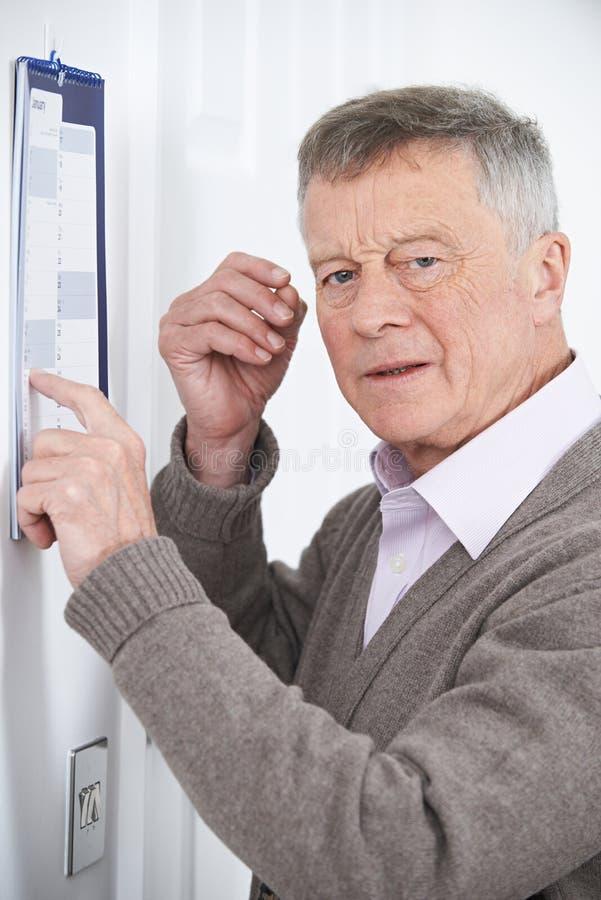 Confused старший человек при слабоумие смотря календарь стены стоковые изображения rf