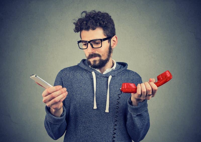 Confused человек с старыми и новыми телефонами стоковые фото