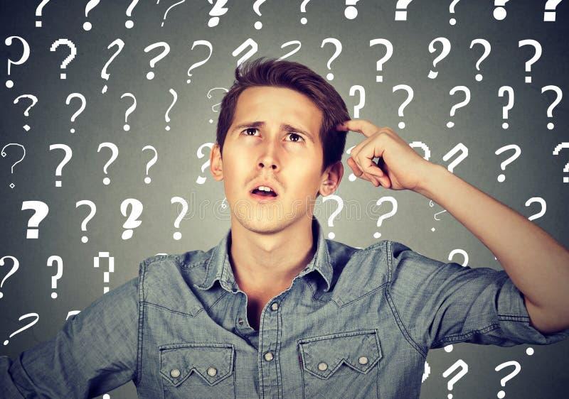 Confused человек имеет слишком много вопросов и нет ответа стоковое фото rf
