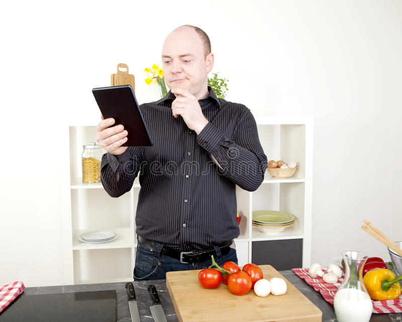 Confused человек читая его таблетку пока варящ стоковое изображение
