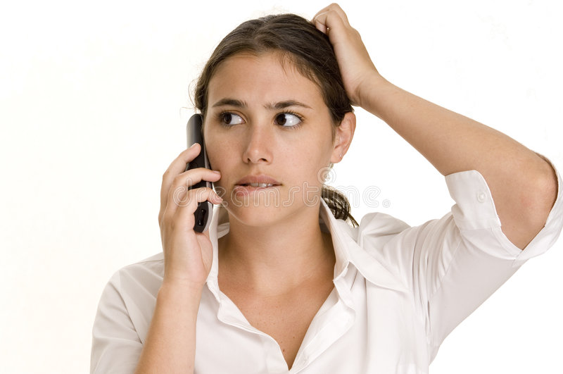Confused. A young woman scratches her head and bites her lip when a phone call confuses her royalty free stock image