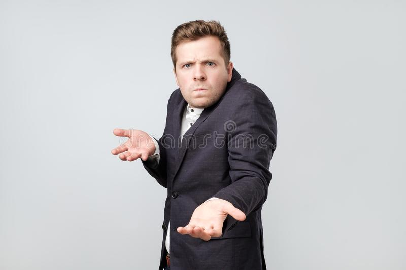 Confused angry young elegant man gestures in bewilderment, expresses negative emotions. stock photography
