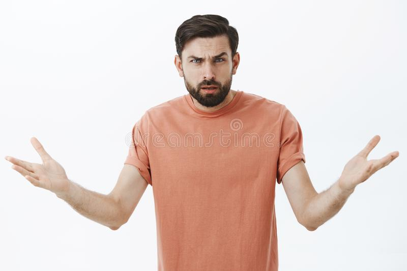 Confused and annoyed angry bearded boyfriend cannot understand why arguing, frowning with clueless emotions shrugging. Raising hands sideways in dismay, asking stock photos
