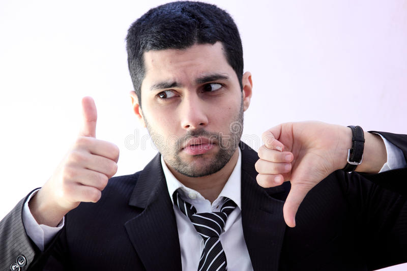 Confused arab business man with thump up and thump down. Arab business man wearing black suit with thump up and thump down hand stock photos