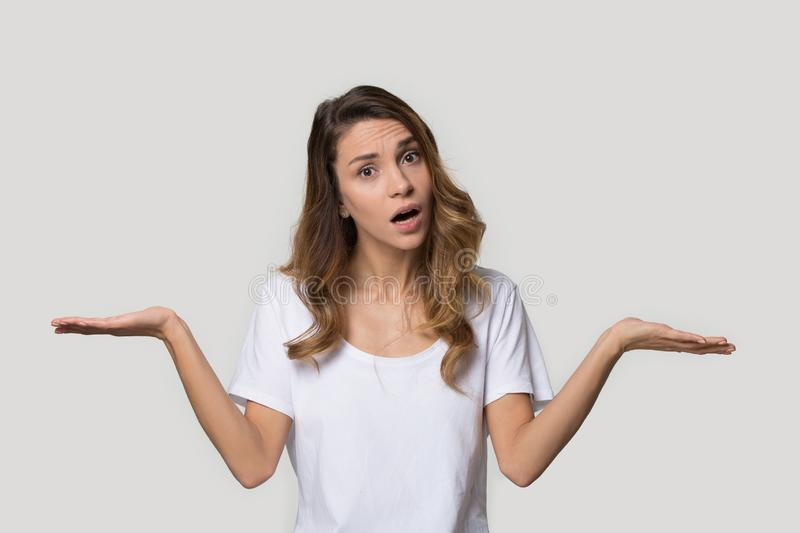Confused attractive young woman shrugging shoulders, looking at camera royalty free stock photos
