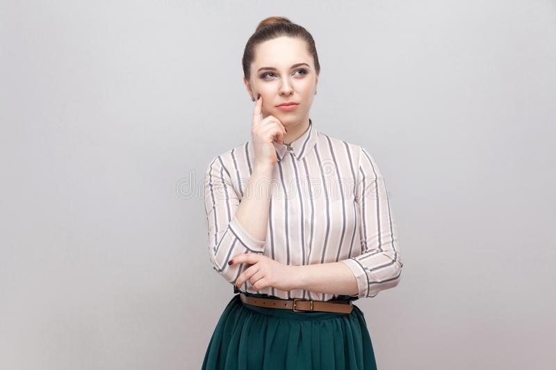 Confused beautiful young woman in striped shirt and green skirt with makeup and collected ban hairstyle, standing thoughtful and stock image