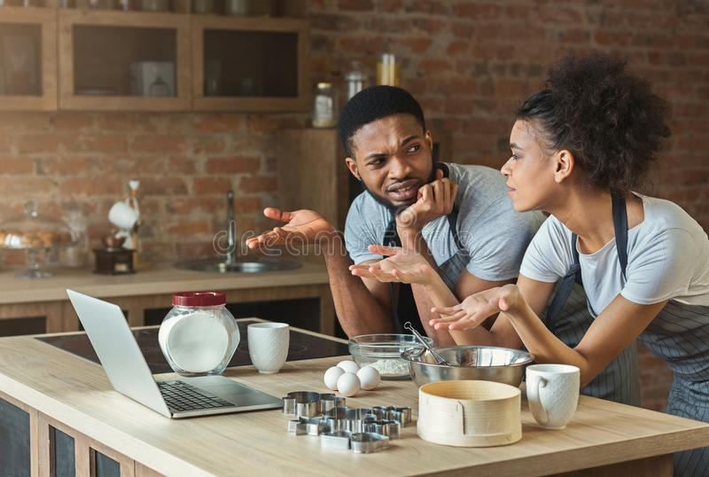 Confused black couple cooking pastry with recipe on laptop. In loft kitchen at home stock photography