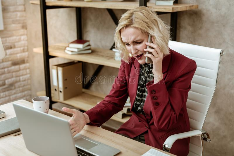 Confused blonde adult lady dealing with unprofessional behavior at work. Reading necessary information. Confused blonde adult lady dealing with unprofessional stock image