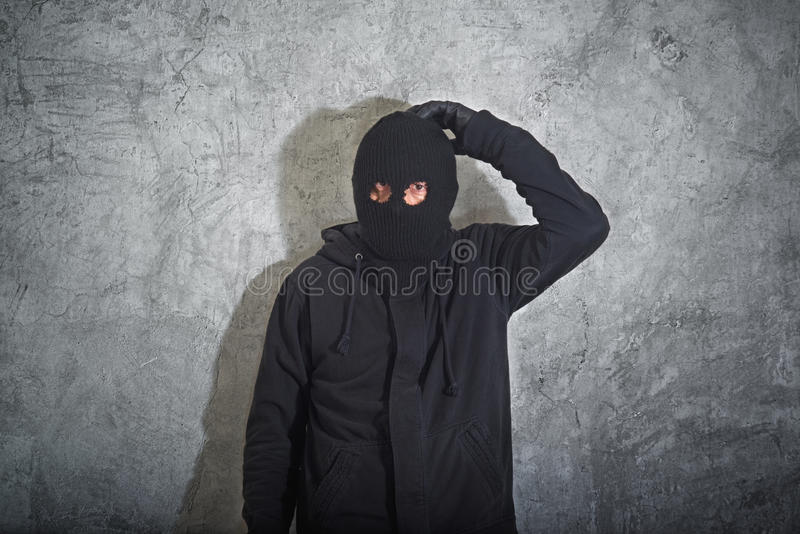 Confused burglar. Concept, thief with balaclava caught and arrested in front of the grunge concrete wall stock image