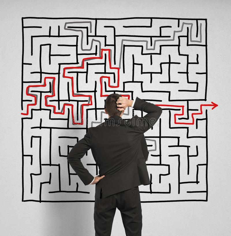 Confused business man seeks a solution to the labyrinth stock images