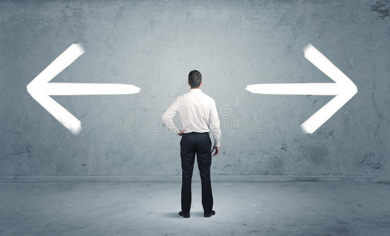 Confused business person choosing the way. A businessman in doubt, having to shoose between two different choices indicated by arrows pointing in opposite royalty free stock photo