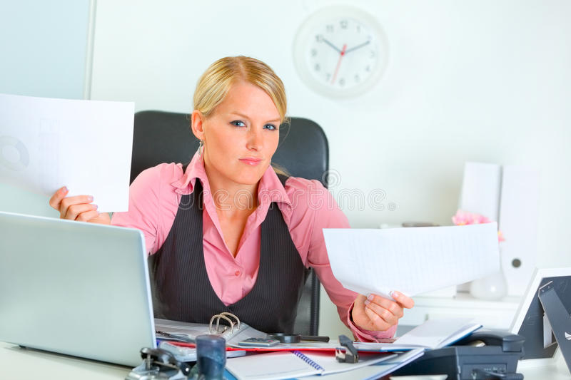 Confused business woman at office desk stock image