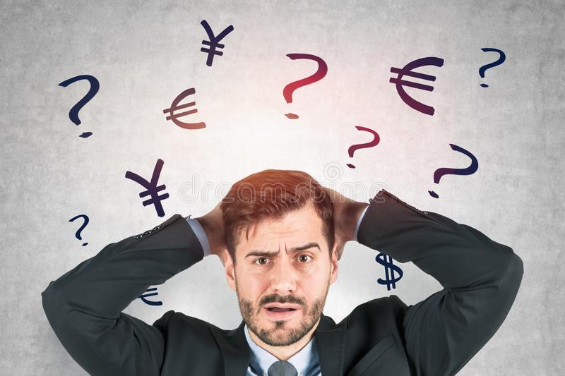Confused businessman, currency signs stock photos