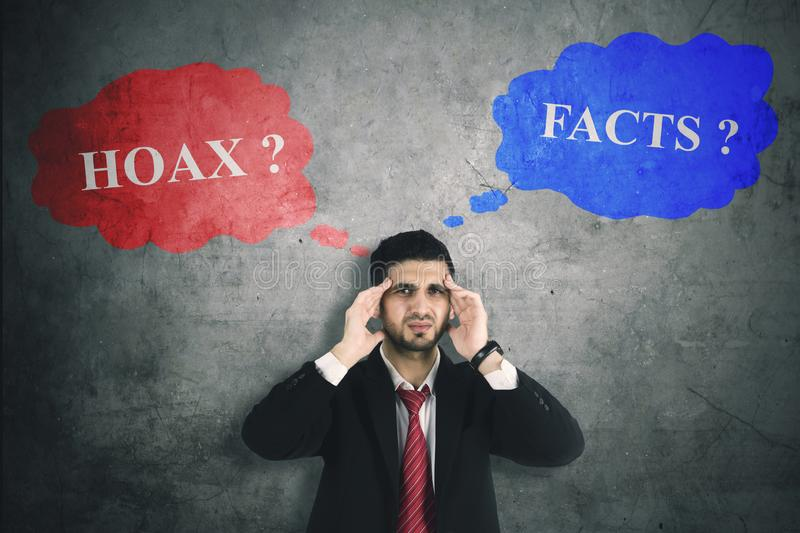 Confused businessman with hoax or fact. Picture of confused businessman making a decision with hoax or fact while standing in the studio royalty free stock images