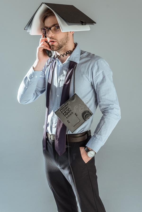 Confused businessman holding notebook on his head while talking on phone royalty free stock image