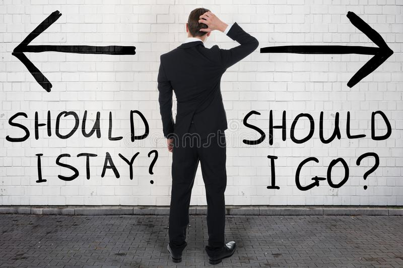 Confused Businessman Looking At Should I Stay Or Go Text. Rear view of confused businessman looking at should I stay or go text royalty free stock image